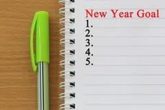笔记本和新年目标文本在棕色木f被安置 库存照片