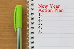 笔记本和新年行动纲领文本在棕色w被安置 免版税库存照片