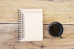 笔记本和无奶咖啡在黑杯子在木桌上 库存照片