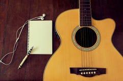 笔记本和木铅笔在吉他 免版税库存照片