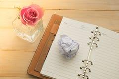 笔记本和桃红色玫瑰在玻璃花瓶在木背景 免版税库存照片