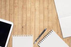 笔记本和片剂在木桌上 免版税库存图片