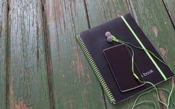 笔记本和电话有耳机的在绿色木桌上 库存图片