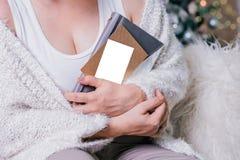 笔记本和空的明信片在妇女的手上在圣诞节闪烁背景 免版税库存图片