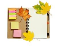 笔记本和笔与干燥秋叶 库存图片