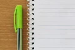 笔记本和笔在一个棕色木地板被安置 免版税库存图片