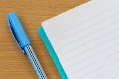 笔记本和笔在一个棕色木地板被安置 库存图片