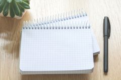 笔记本和笔在一张木桌上 免版税库存照片