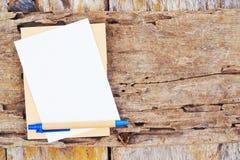 笔记本和笔在木委员会 免版税库存照片