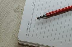 笔记本和笔在构成在红色和白色 图库摄影