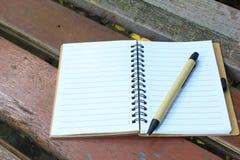 笔记本和笔在棕色长凳 免版税库存图片