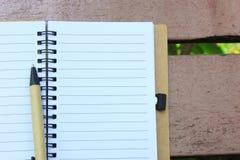 笔记本和笔在棕色长凳 免版税图库摄影