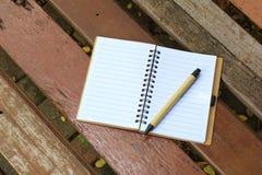 笔记本和笔在棕色长凳 免版税库存照片