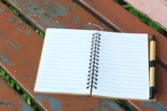 笔记本和笔在棕色长凳 库存图片