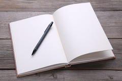 笔记本和笔在灰色木背景 免版税库存照片
