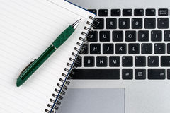 笔记本和笔在膝上型计算机键盘,关闭 库存照片