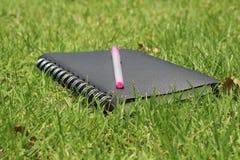 笔记本和笔在草 免版税库存图片