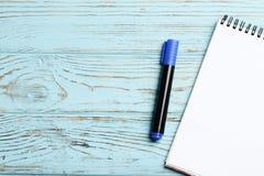 笔记本和笔在蓝色木背景 E 库存图片