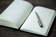 笔记本和笔纪录的在木背景 免版税库存照片