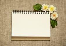 笔记本和翠菊在角落 免版税库存照片