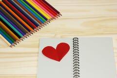 笔记本和色的铅笔在木背景 免版税库存图片