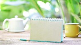 笔记本和茶在木桌上 库存图片