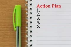 笔记本和行动纲领文本在一棕色木flo被安置 免版税库存图片