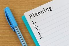 笔记本和计划文本在一个棕色木地板被安置 库存图片