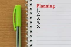 笔记本和计划文本在一个棕色木地板被安置 库存照片
