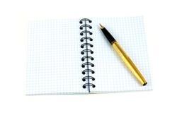 笔记本和金黄钢笔 免版税图库摄影