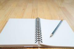 笔记本和铅笔在木板 图库摄影