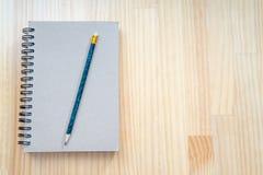 笔记本和铅笔在木板 免版税库存图片