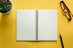 笔记本和铅笔在黄色书桌上 免版税库存照片