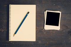 笔记本和铅笔有框架照片的在木桌背景 图库摄影