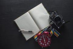 笔记本和铅笔有老照相机葡萄酒的在老木书桌上 库存图片