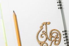笔记本和黄色铅笔有木公鸡的在一白色backgroun 免版税库存照片