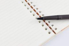 笔记本和黑笔 免版税库存图片