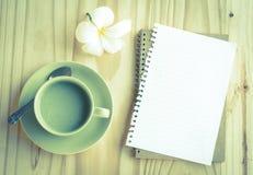 笔记本和绿茶杯子在桌上 免版税库存图片