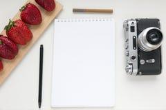 笔记本嘲笑为与老照相机、笔和红色草莓的艺术品 顶视图 安置文本 免版税库存照片