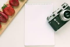 笔记本嘲笑为与老照相机、笔和红色草莓的艺术品 顶视图 安置文本 库存图片