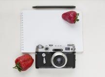 笔记本嘲笑为与老照相机、笔和红色草莓的艺术品 顶视图 安置文本 库存照片