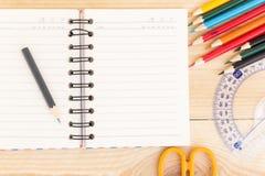 笔记本在木桌上的纸和学校或者办公室工具 免版税库存图片