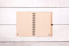 笔记本在木桌上的被回收的纸空白 免版税库存照片