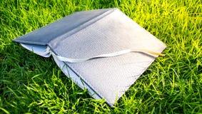笔记本在草皮 免版税库存图片