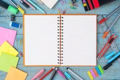 笔记本在葡萄酒木头桌上的纸和学校或者办公室工具 库存照片