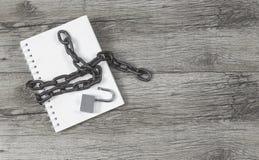 笔记本开锁了与在木背景的一条钥匙链 免版税库存照片