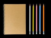 笔记本或演讲笔记本在棕色盖子和黑顶头笔 库存照片