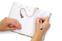笔记本打开与女性手写 免版税库存照片
