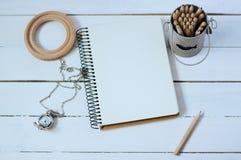 笔记本木白色桌 免版税图库摄影