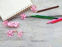 笔记本桃红色花和铅笔在木背景 库存图片